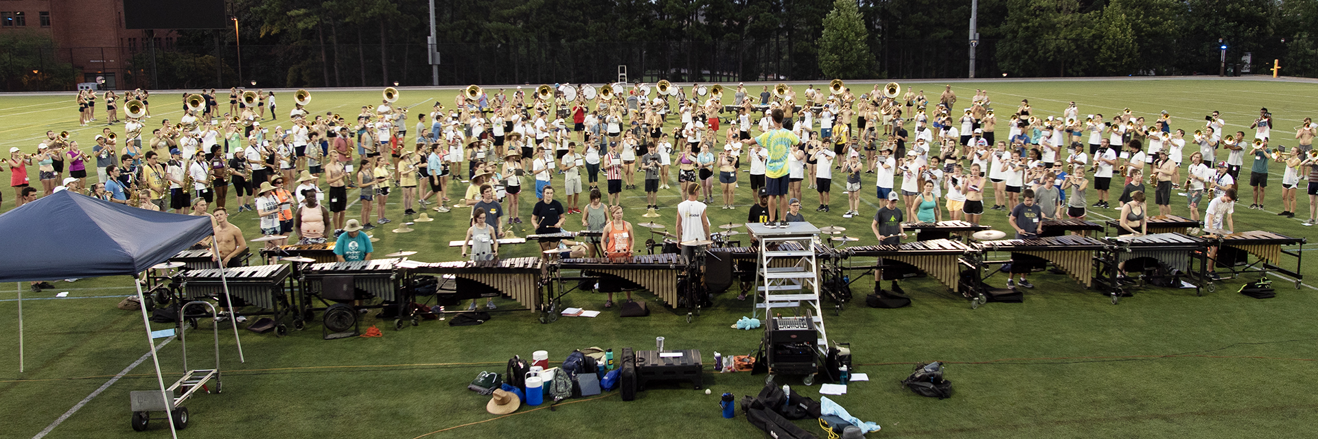 Students outside on a field at band camp.