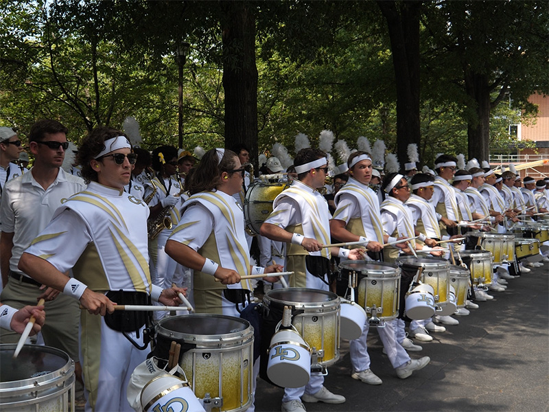 The Drumline playing on the street outside the stadium before a football game starts.