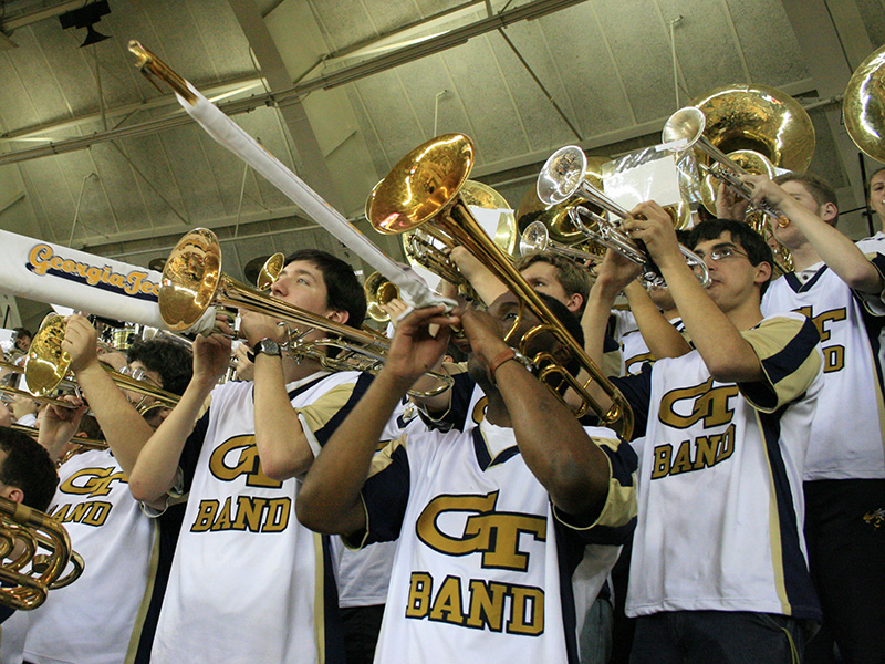 Trombonists in the Pep band performing at a basketball game.