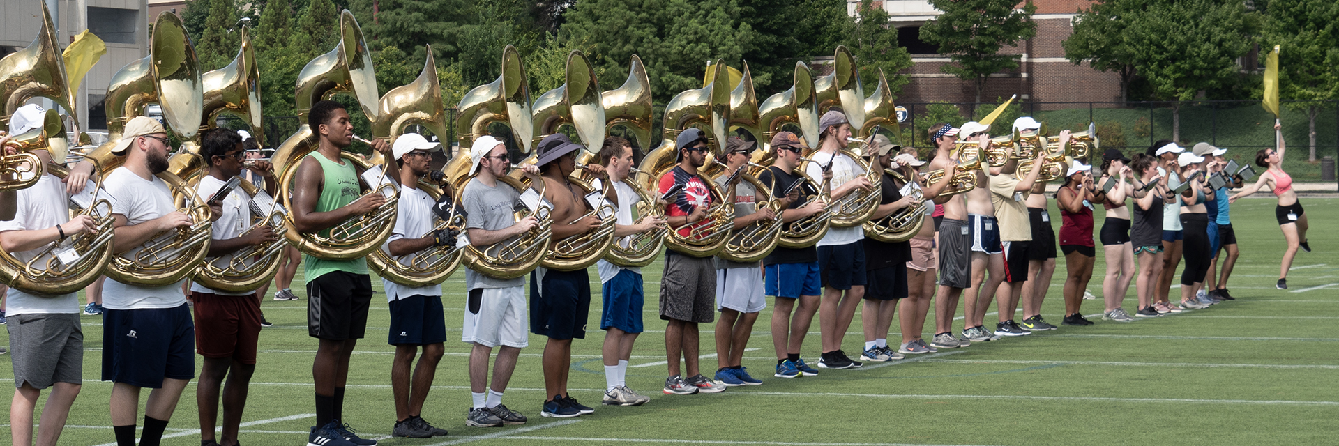 Plain clothes students practicing for a marching band performance in a field.