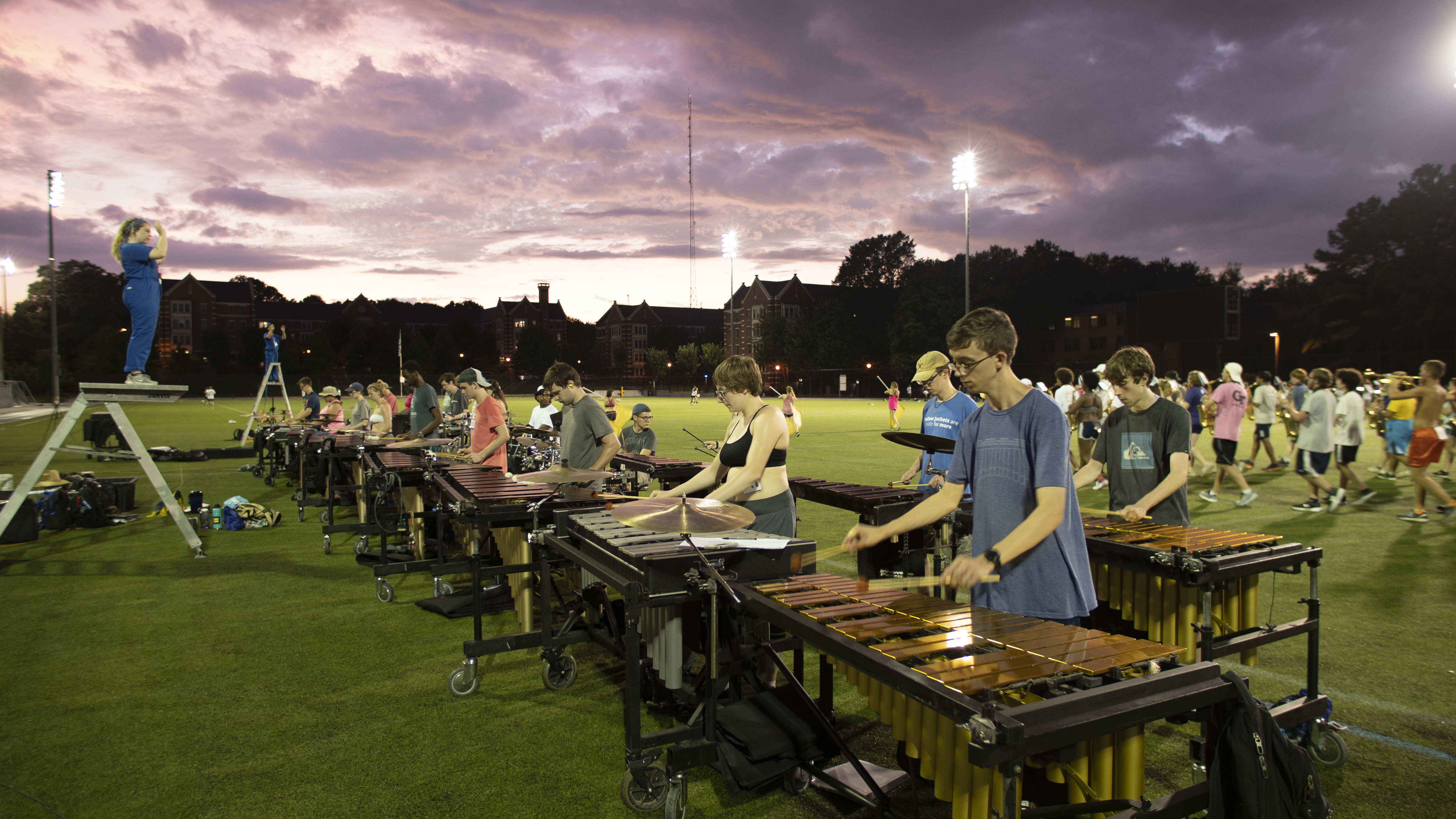 Percussion players practicing on Stamps field under an evening sky.