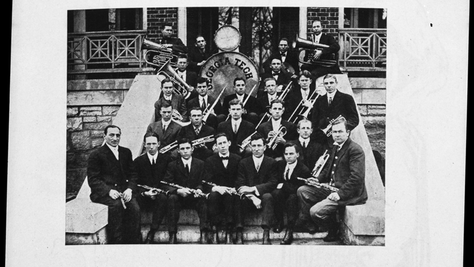 Members of the band posing on steps with their instruments while wearing dark suits.