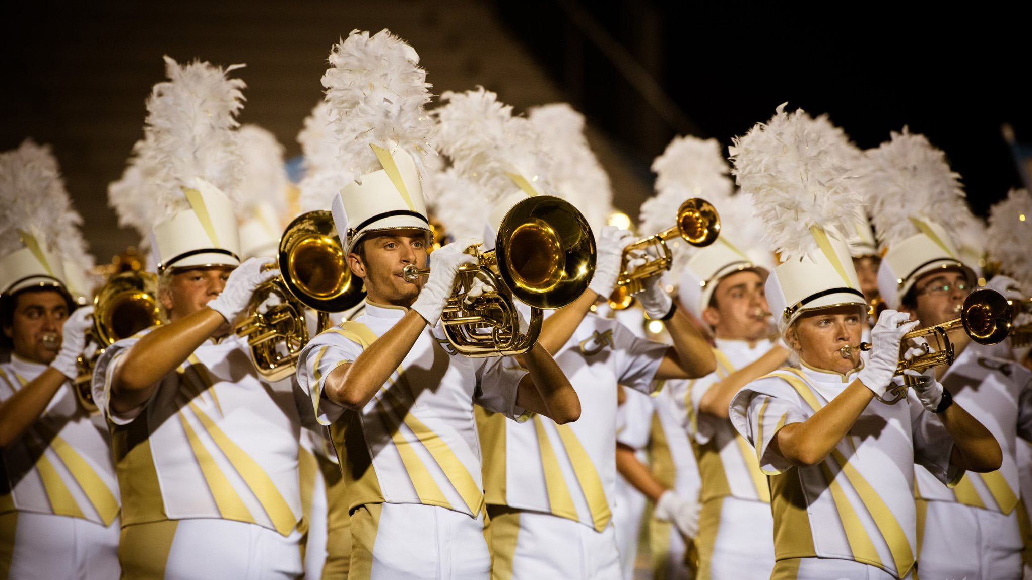 A group of brass players in the middle of a routine.