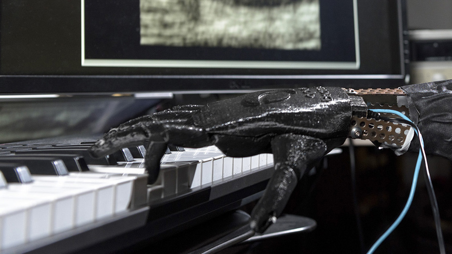 A robotic hand playing the piano.