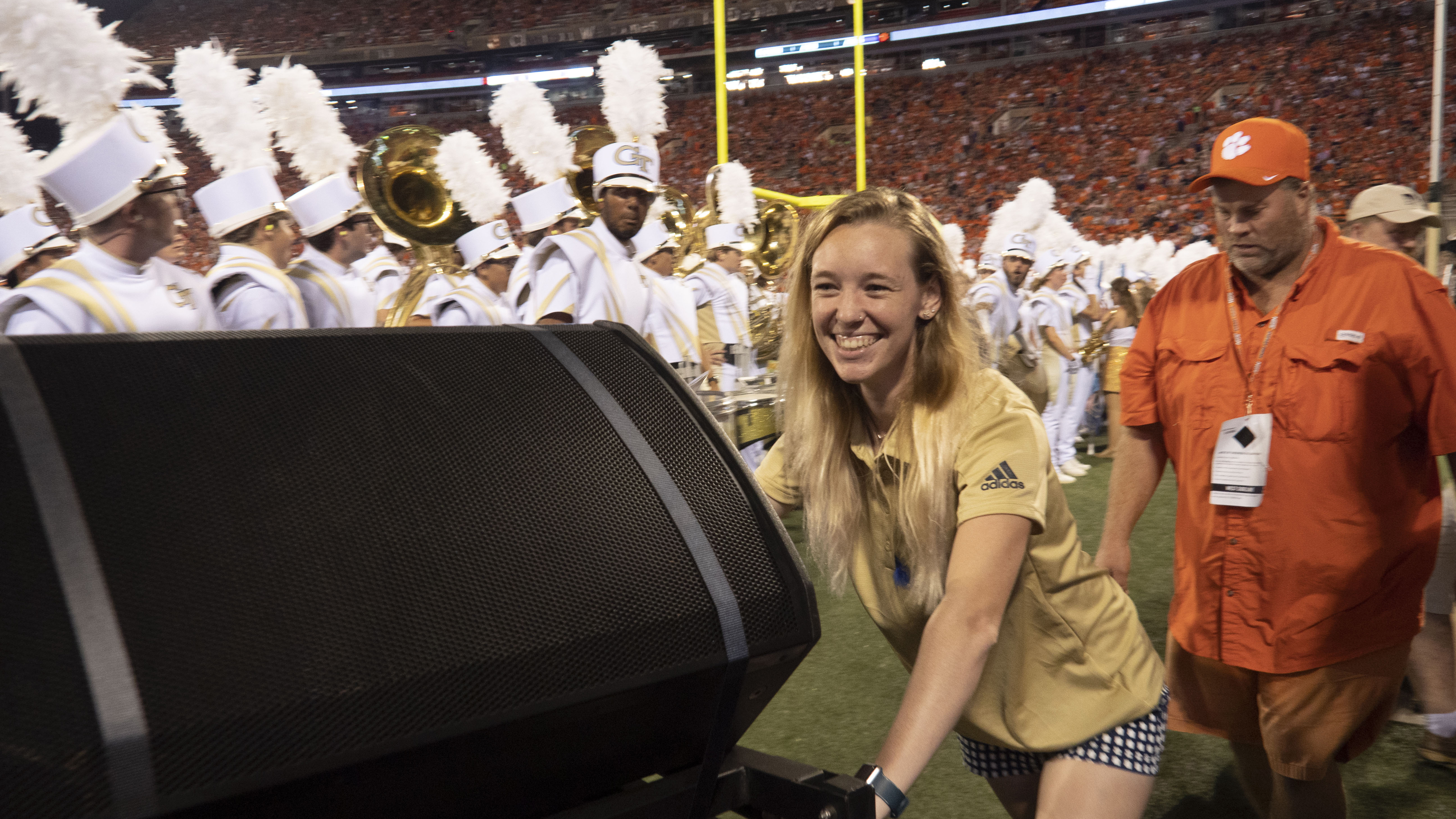 A staff assistant pushes a speaker off the field while the band sets up.