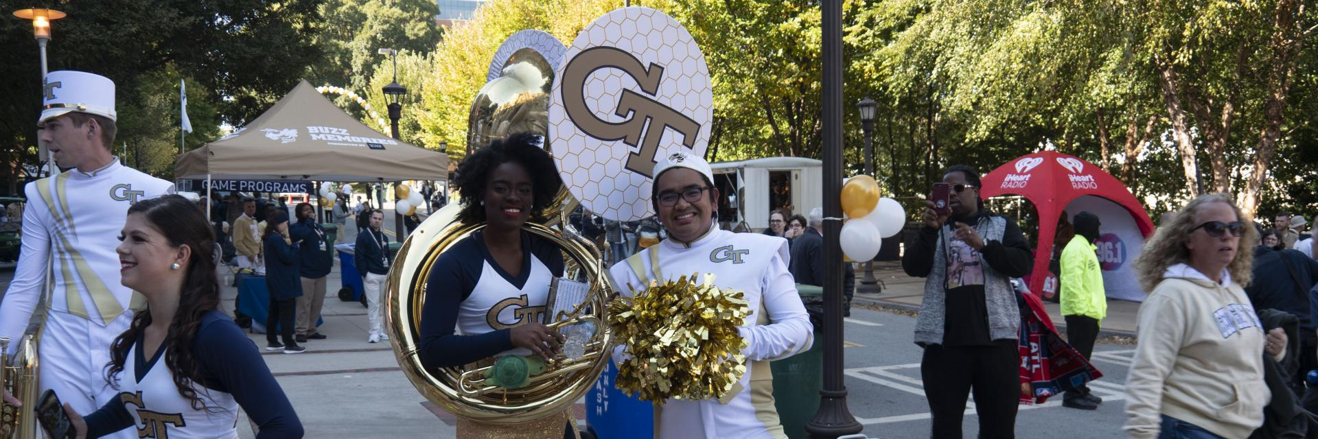 A cheerleader and a tuba player trade instrument and pom poms to pose for a picture.