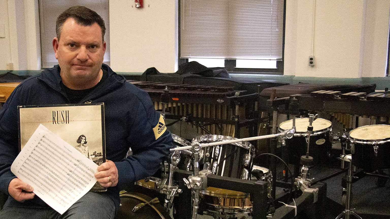 "Chris Moore sits in front of percussion instruments holding the sheet music for the song ""Tom Sawyer"" and his vinyl copy of ""Permanent Waves."""