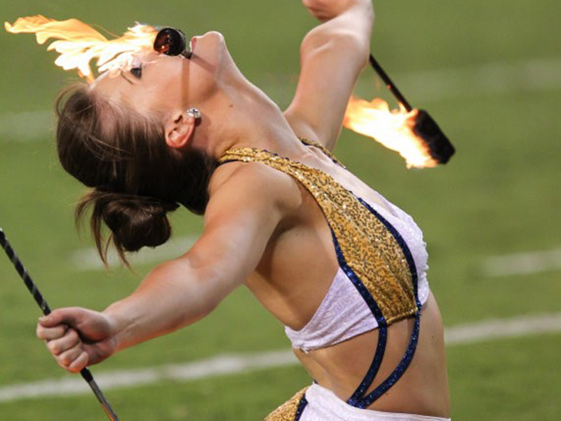 A twirler holding flaming batons in both her hands and teeth.